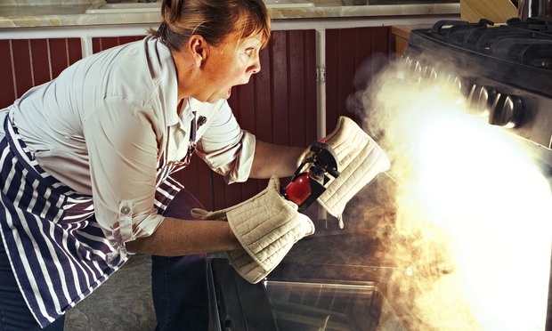 Woman opening a burning oven